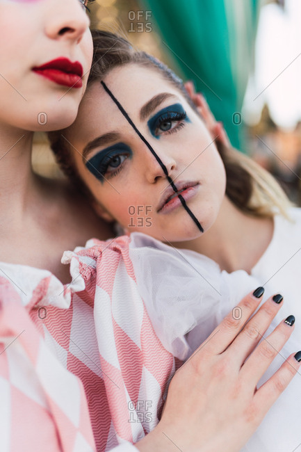 Beautiful young woman with theatrical makeup embracing friend and looking at camera while standing near merry-go-round on fairground