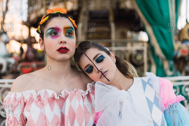 Beautiful young woman with theatrical makeup embracing friend while standing near merry-go-round on fairground