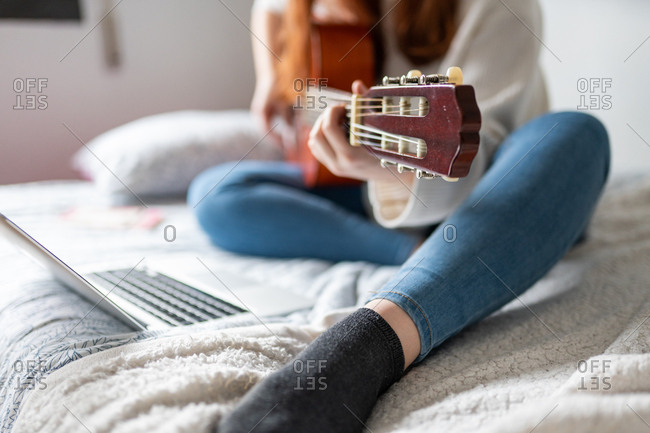 Pretty young woman with acoustic guitar browsing modern laptop while sitting on comfortable bed