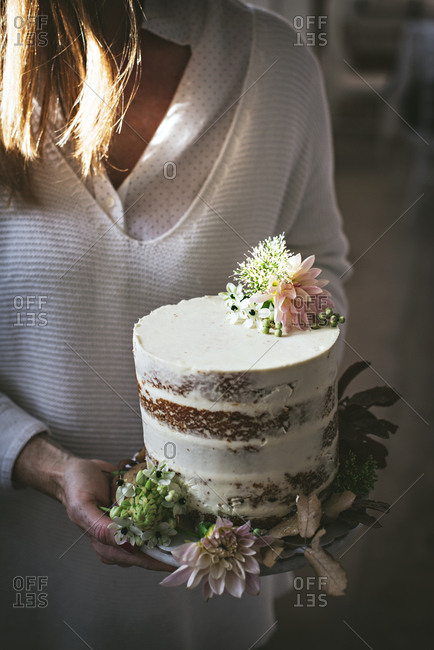 Side view of crop happy lady holding dish with tasty cake decorated by chrysanthemum bud and dry leaves in room