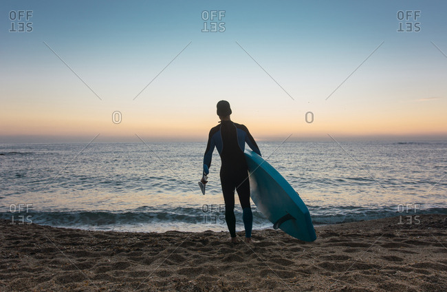 Man practicing paddle surfing with neoprene in a sunrise on a paradisiacal beach