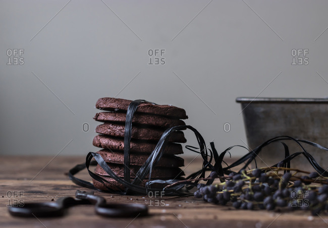 Pile of tasty gluten free chocolate biscuits tied with black thread standing on shabby lumber tabletop near scissors