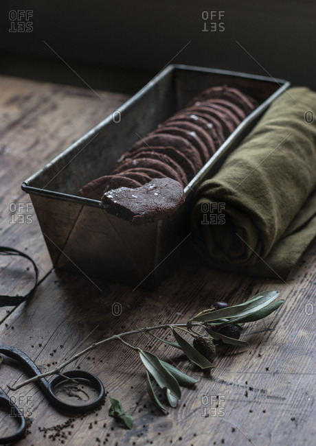 Small dry olive sprig lying on wooden tabletop near metal box with delectable gluten free chocolate biscuits and soft towel