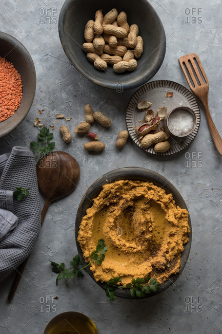Bowl with delectable lentil hummus with carrot and fresh peanuts standing on gray plaster surface