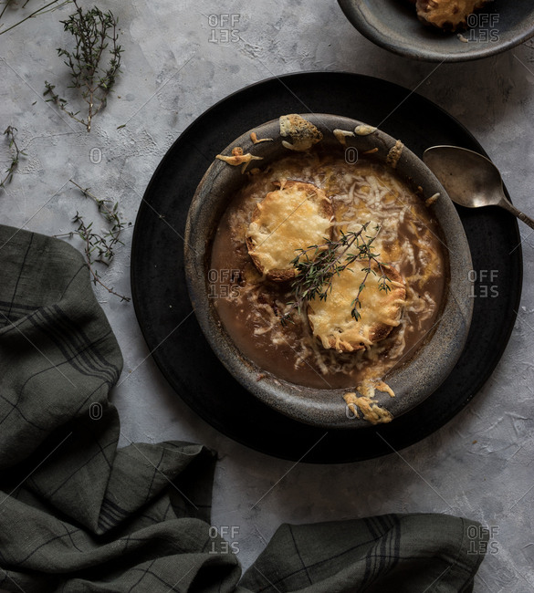 Metal bowl with palatable French onion soup standing near towel on gray plaster surface