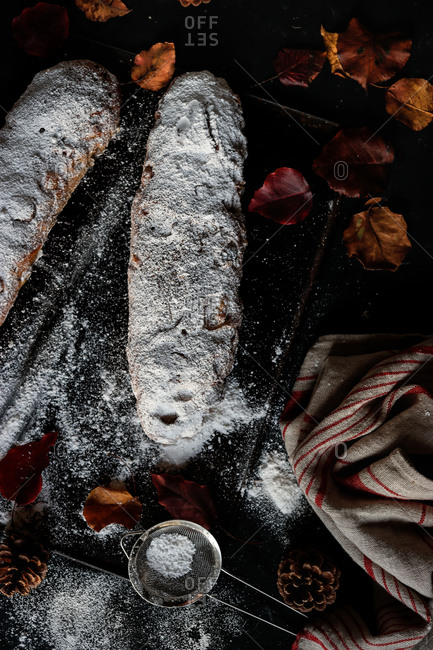 Delicious fresh Stollen covered with powdered sugar lying on dark tabletop