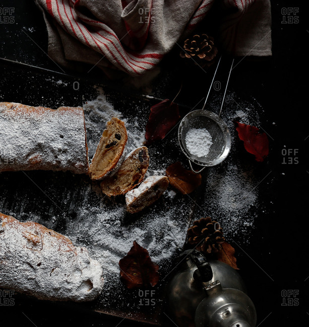 Pieces of delicious fresh Stollen covered with powdered sugar lying on dark tabletop