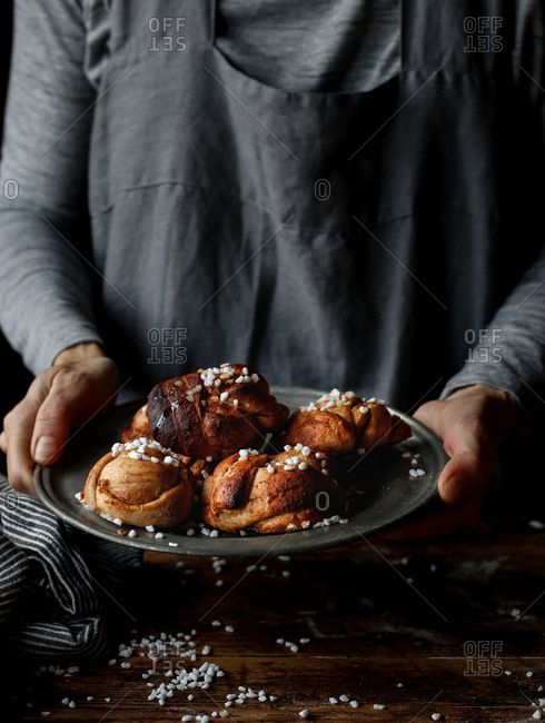 Anonymous female holding metal plate with heap of delicious Swedish cardamom buns over lumber tabletop