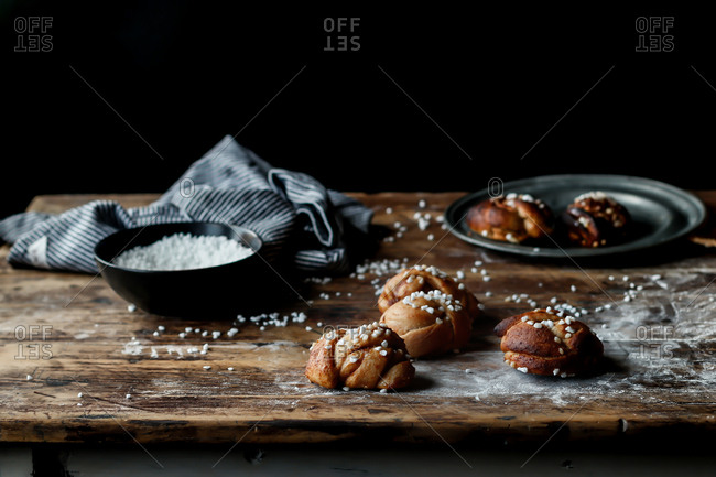 Closeup Swedish cardamom buns with sugar crystals lying on metal grating on shabby lumber table