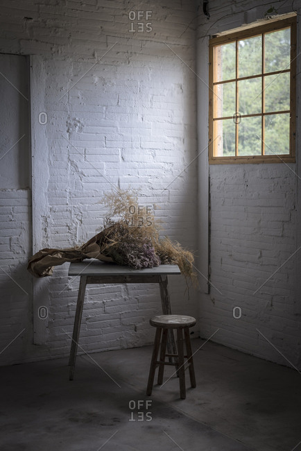 Concept of bouquet of dry coniferous twigs in craft paper on table near stool in grey murk room with brick walls