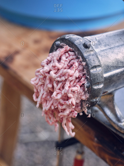 Closeup metal mincing machine with fresh ground meat standing on table