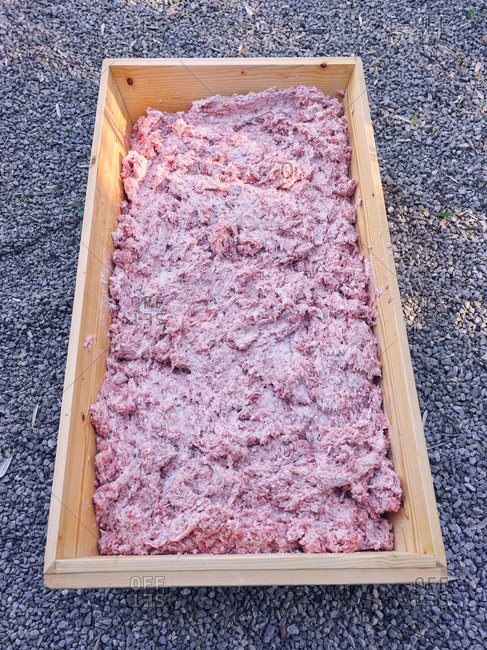 Huge timber trough with fresh minced meat standing on ground on street