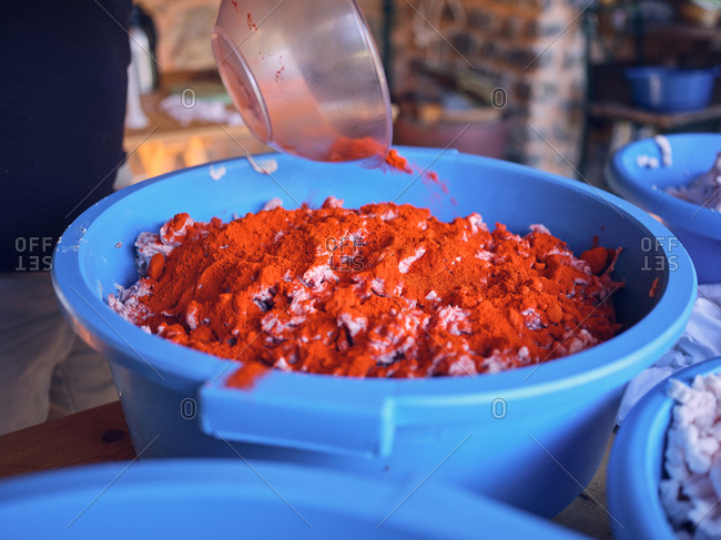 Aromatic spices spilling in plastic basin with raw fresh minced meat