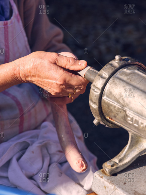 Unrecognizable elderly woman using metal machine to fill animal bowel with minced meat