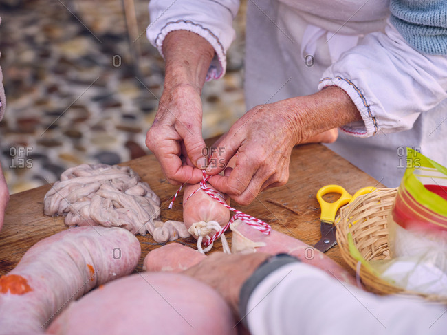 Crop elderly woman tying striped thread on fresh natural sausage while standing near wooden table