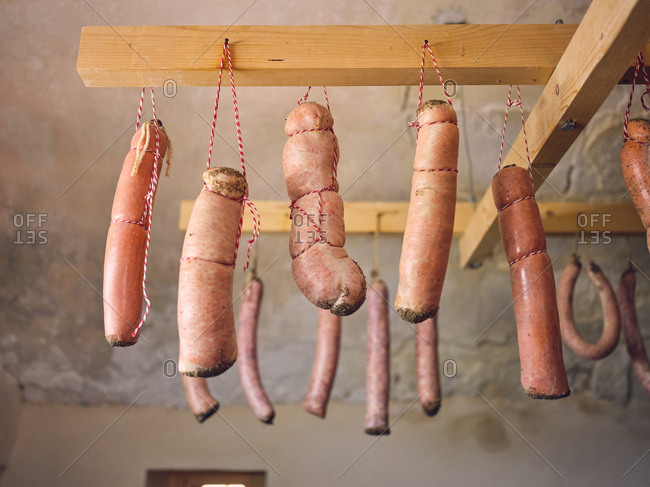 Bunch of fresh natural sausages hanging on boards under ceiling of shed