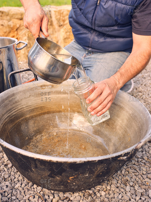 Unrecognizable man pouring fresh clean water into glass jar while sitting near cauldron in yard
