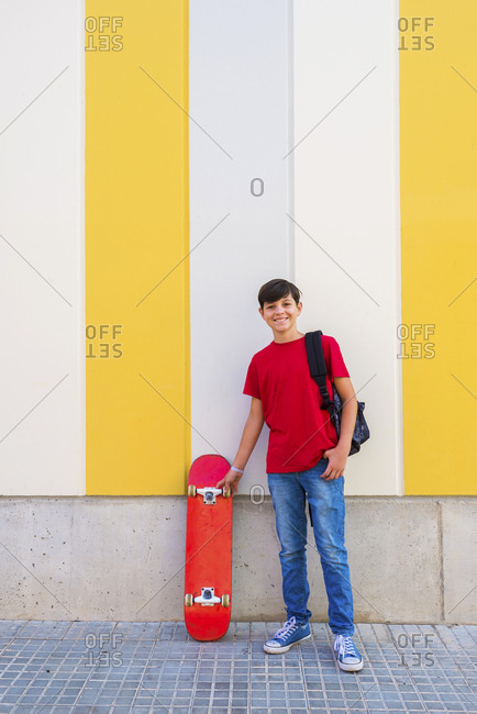 Front view of a young boy wearing casual clothes standing against a colored wall while holding a skateboard and smiling
