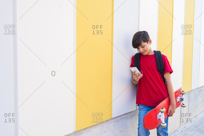 Young boy wearing casual clothes standing against a colored wall while using a mobile phone