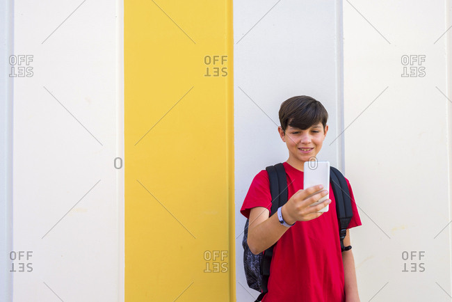 Casual modern youngster with backpack standing on street and taking selfie with smartphone