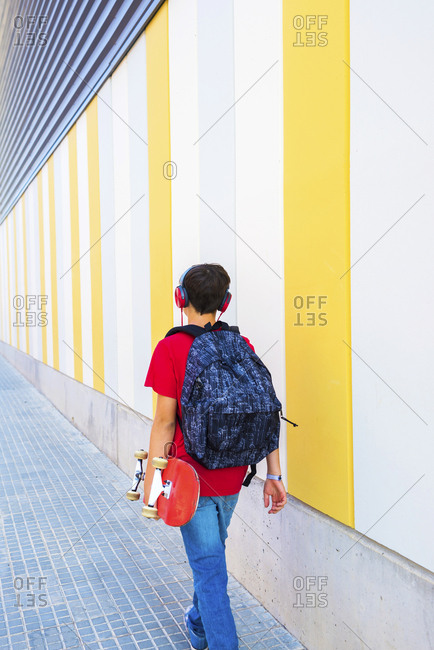 View of a young boy wearing casual clothes walking against a colored wall while holding a skateboard