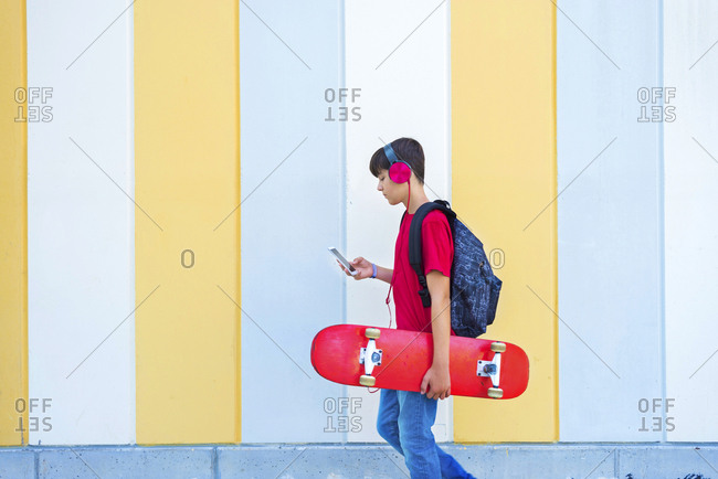 Side view of a young boy wearing casual clothes walking against a colored wall while using a phone