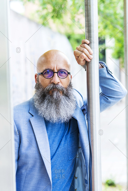 Front view of a mature trendy bearded hipster leaning on a pole outdoors while looking to camera