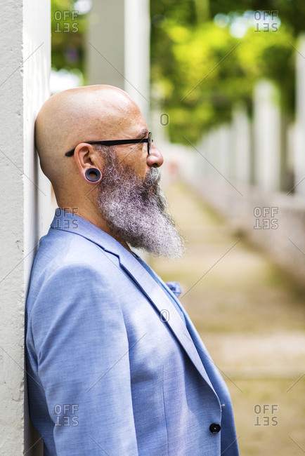 Side view of a beaded hipster man leaning on a wall while looking away
