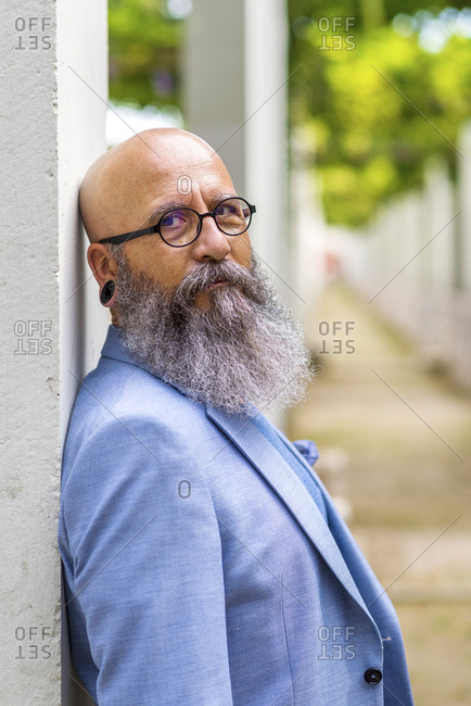 Side view of a beaded hipster man leaning on a wall while looking camera
