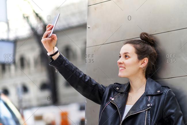 Woman taking selfie near column