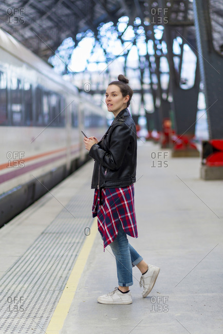 Woman with smartphone on railway station