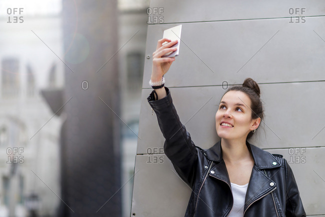 Cute young female in trendy outfit smiling and taking selfie while leaning on pillar of modern railway station