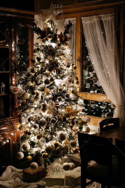 Wonderful Christmas tree decorated with various baubles and bright fairy light garland standing near window in stylish room at night