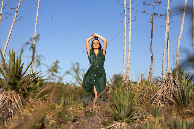 Pretty young model in green dress holding hands over head while standing near thin exotic trees and bushes on sunny day in nature
