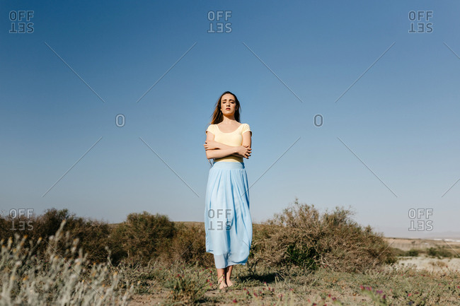Cute young woman keeping eyes closed and crossed arms while standing in wonderful meadow against clear blue sky on windy day