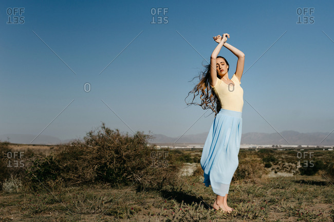 Cute young woman keeping eyes closed and hands raised while standing in wonderful meadow against clear blue sky on windy day