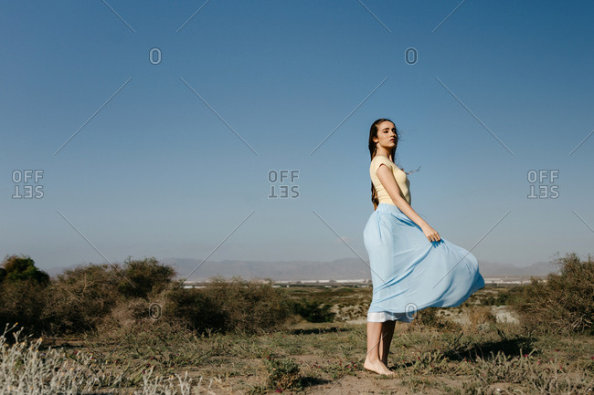 Side view of beautiful young woman standing in wonderful meadow against cloudless blue sky