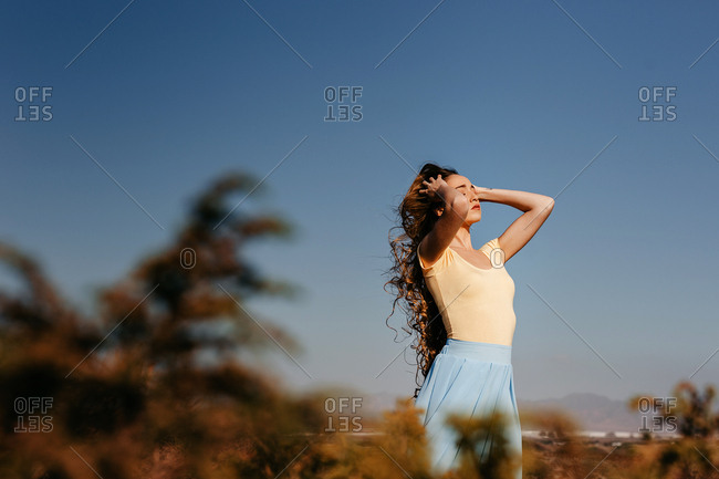 Cute young woman keeping eyes closed and touching hair while standing in wonderful meadow against clear blue sky on windy day