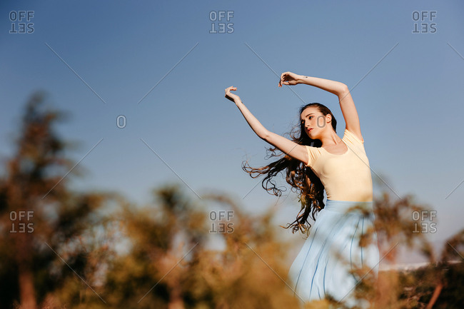 Cute young woman with hands raised while standing in wonderful meadow against clear blue sky on windy day