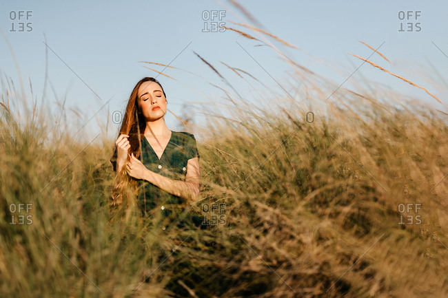 Pretty young female keeping eyes closed while standing in tall field grass on sunny day in majestic countryside