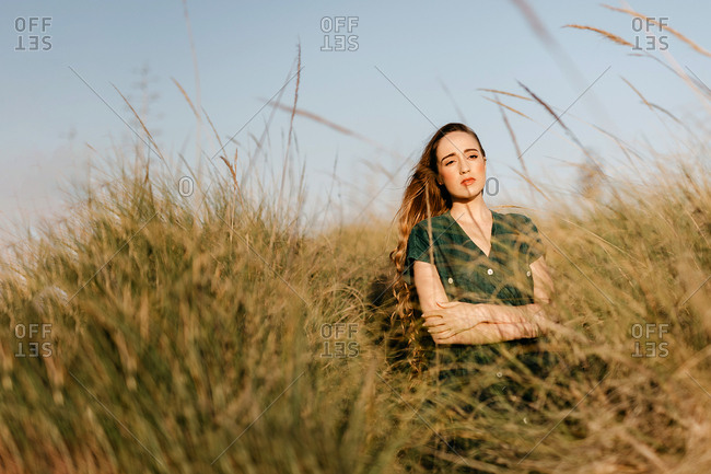 Pretty young female looking away while standing in tall field grass on sunny day in majestic countryside