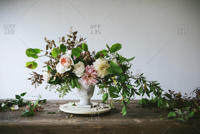 Concept of bouquet of dry and fresh roses, chrysanthemums and plant twigs in retro vase on wooden board on grey background