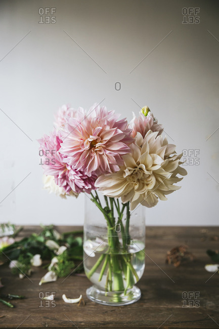Wooden table with kitchenware and bouquet of fresh blooms in vase with water near white wall