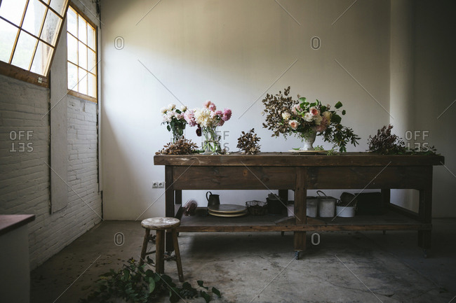 Wooden table with kitchenware and bouquets of fresh blooms in vases with water near white wall