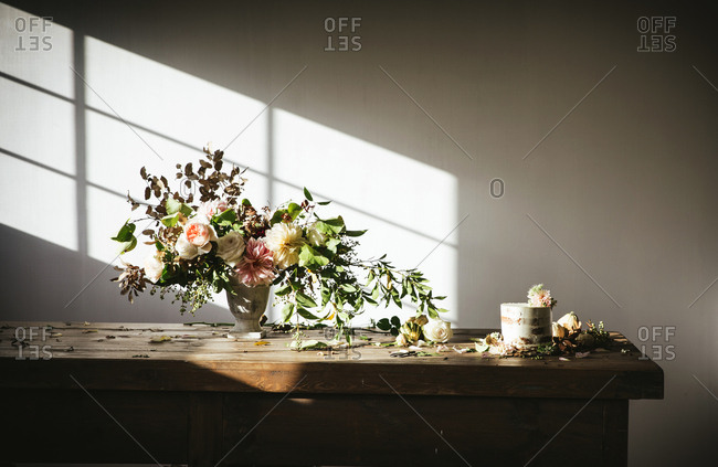 Dish with tasty cake decorated bloom bud on wooden table with bunch of chrysanthemums, roses and plant twigs in vase between dry leaves on grey background