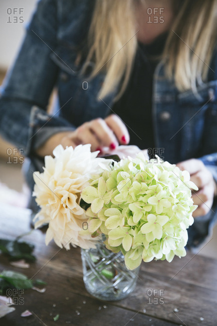 Happy lady near wooden table with bunches of fresh chrysanthemums, roses and plant twigs in vases on grey background