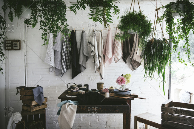 Wooden table with bunch of fresh pink chrysanthemums and white hydrangea in vase between frying pan and kitchenware near dish cloths hanging on twist with pins