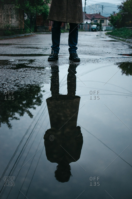 Unknown man reflected upside down in water on a street