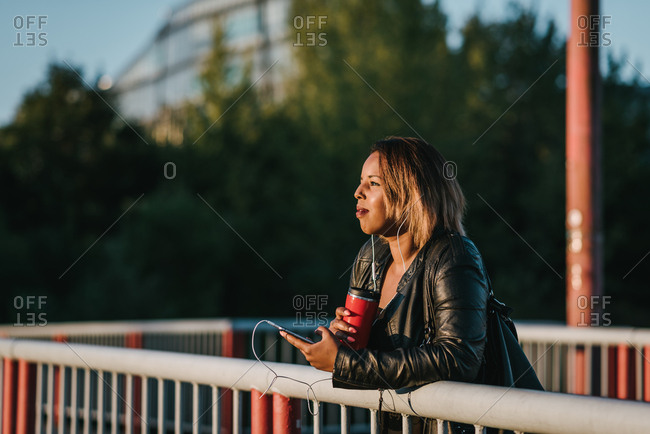 Black woman with short blonde hair leaning on a fence and enjoying in sunset