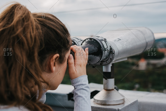 Young female tourist looking through tower viewer